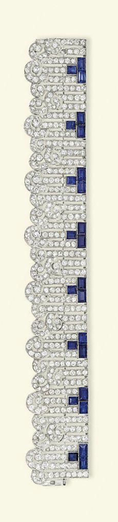 AN ART DECO SAPPHIRE & DIAMOND BRACELET   Designed as a series of brilliant-cut diamond baton links with scrolling terminals & rectangular-shaped sapphire three-stone accents, ca 1930, 19.2 cm long.