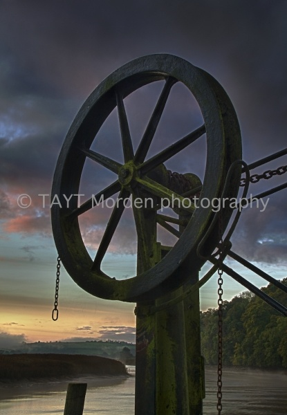John S W Taylor  COTEHELE CRANE @ DAWN  Mounted Limited Edition   signed Photographic Print: 2/10  Image captured at Cotehele Quay,   Cornwall - October 2011.  Print: 25 cm wide x 36 cm high  Mount: 37 cm wide x 48 cm high  Neutral double mount   cellophane-wrapped  Authentic photograph printed on   silver-based light sensitive paper.  £65