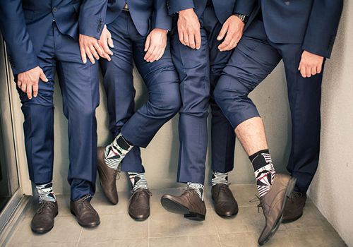 blue suits, crazy socks, brown shoes at a wedding