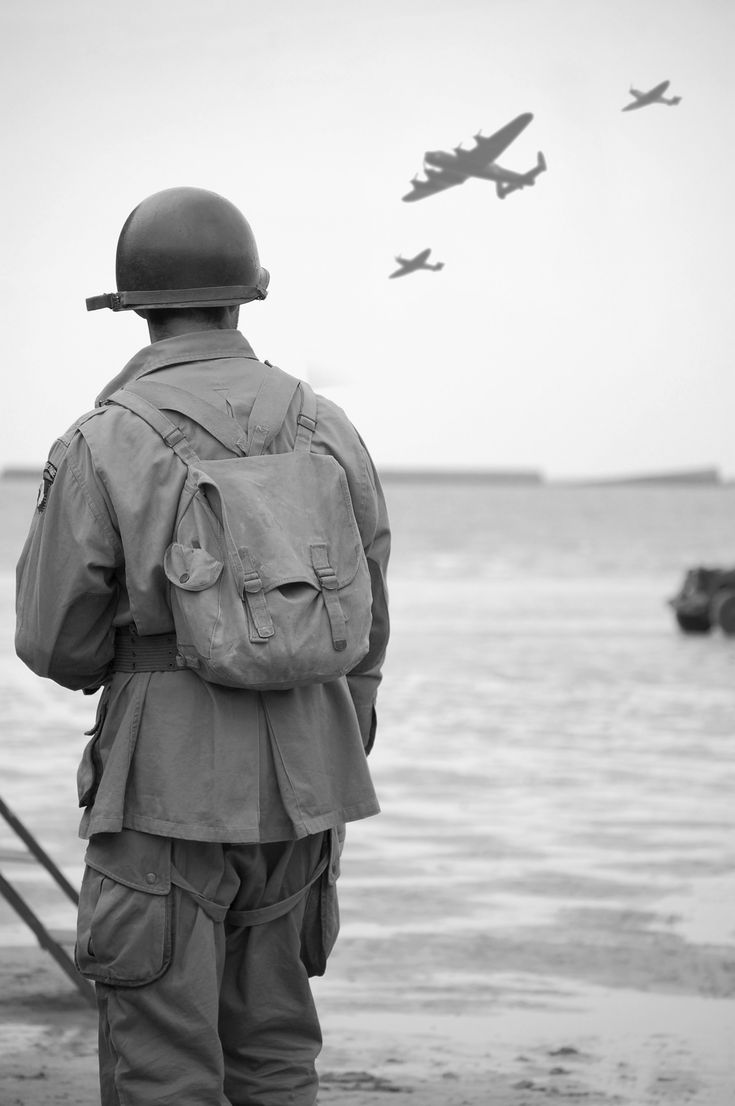 U. S. Army Paratrooper, 101st A/B, on Omaha Beach, Normandy, France, D-Day anniversary commemoration; the aircraft are the Lancaster and 2 Spitfires of the RAF Memorial Flight.