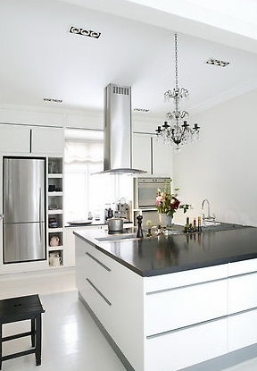 love the addition of a traditional chandelier in this clean, sleek kitchen.