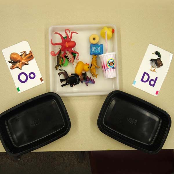 INSTRUCTION This activity involves students sorting objects into bins according to the letter. Students practice the sound that the first letter of the object is. This activity is effective because it gives students opportunity to associate the letters with words that start with that letter and sound, which increases their understanding of the letters.
