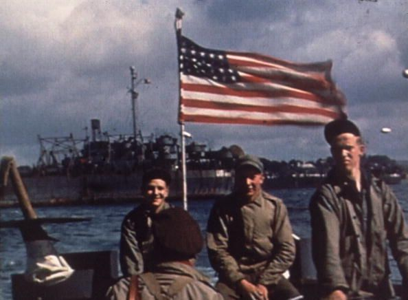 6th June 1944: US troops travel the English Channel on a barge en route to Normandy, France for the D-Day Invasion, World War II. An American flag flies behind them. (Photo by Anthony Potter Collection/Getty Images)