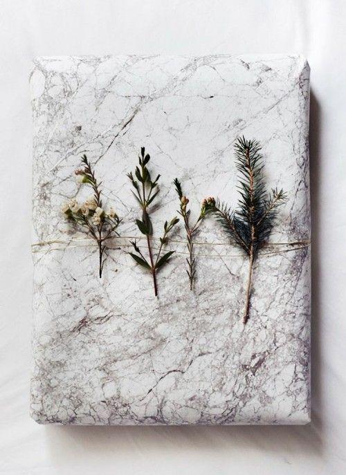 Das Papier zeigt einen der wichtigsten und schönsten Wohntrends, nämlich Marmor. Mit einem Kupferdraht sind kleine Immergrünzweiglein um das Geschenk gewickelt. sweet home