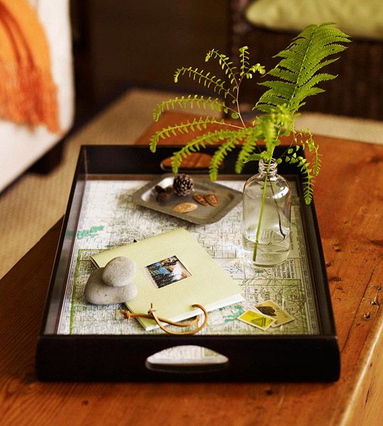 Table Traveler  Keep the memory of a recent vacation alive long after you've returned home. Assemble a collection of vacation mementos to display inside a tray. Line the bottom of a tray with a souvenir map, layer a piece of glass or acrylic on top for protection, and include a small photo album to share your memories.