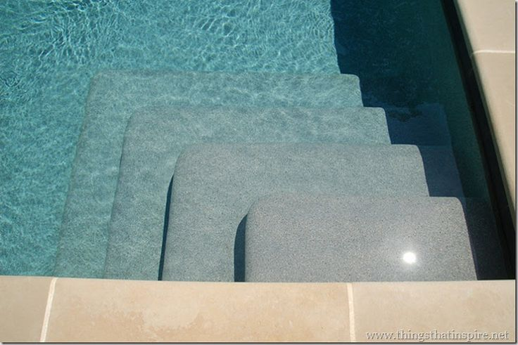 "Things That Inspire shares this info: ""...the steps to the pool  show the different colors that the Pebble Sheen French Grey takes on at different depths. It was a medium gray when it was installed, without water – and as seen on the first step, that's how it appears in very shallow water. However, when there is water at greater depths ( which is the majority of the pool ), the color appears a beautiful and sophisticated blue – not a greeny blue, but a turquoise!"""