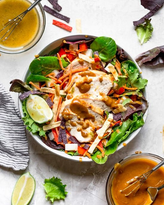 Grilled Chicken Salad with greens and vegetables are tossed in a honey-lime vina…