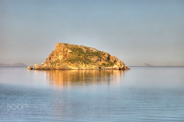 Island in The Sun - I shot this tiny island early in the morning with the sun shining on it giving that golden glow and  reflexion on the surface of the sea. The photo was shot near the coastline on the South part of the island of Syros in Greece. Its name is Strogillo.