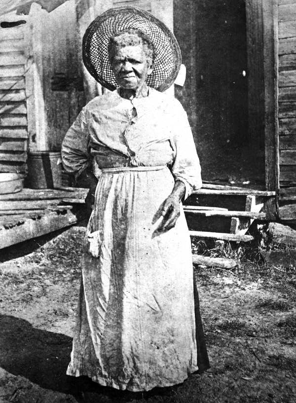 SELINA ROLLINS (1837-1925) standing outside a house - Micanopy, Florida. Selina Rollins was the last surviving former slave in Micanopy, Florida. (year 19--)  Photo: State Archives of Florida.