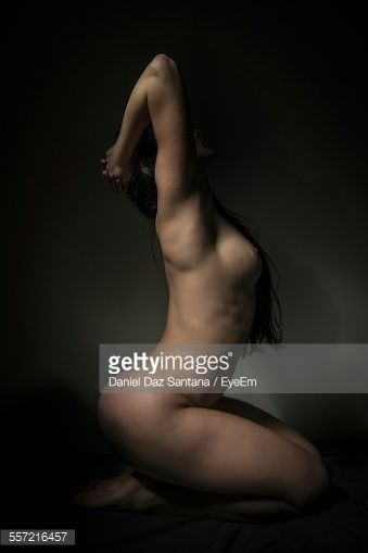 Side View Of Naked Woman Against Colored Background