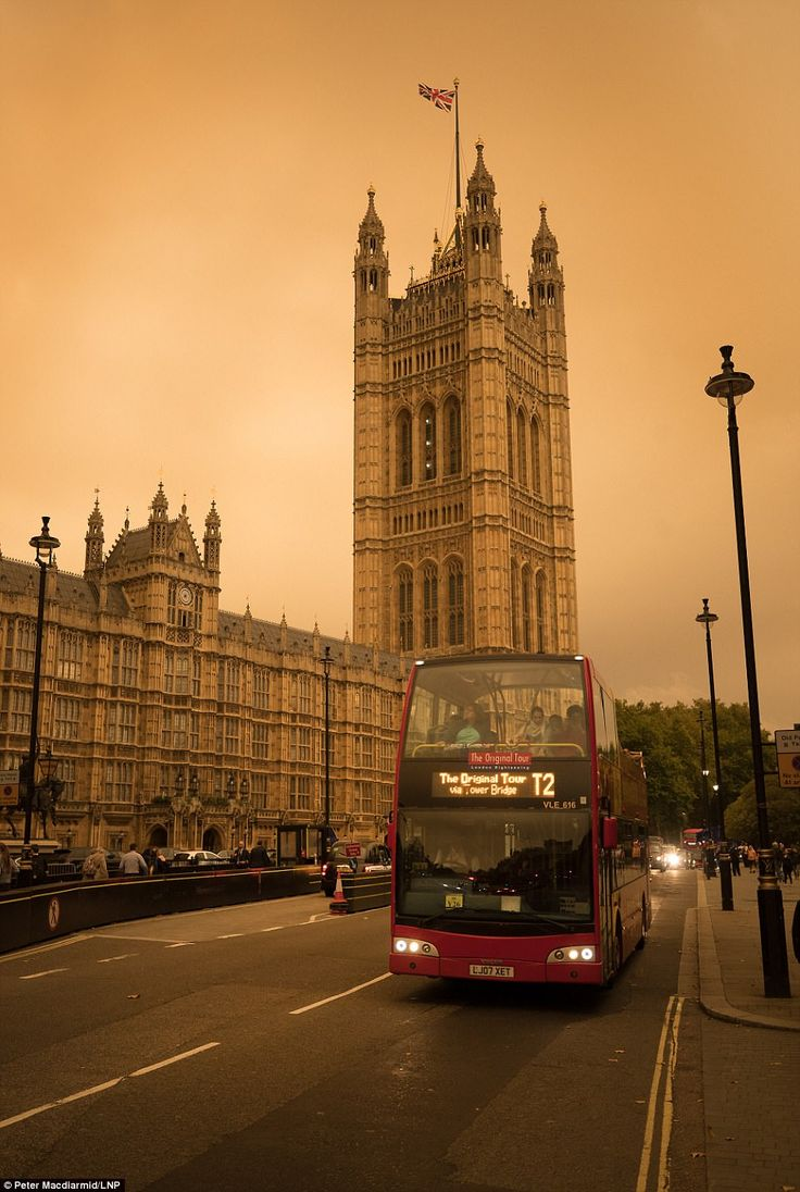 LONDON: A tourist looks up at the sky from the top deck of a London sightseeing bus in Wes...