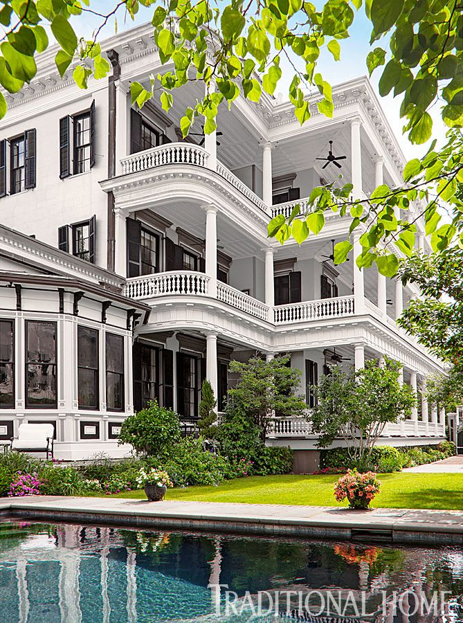 Wide verandas punctuated by elegant balustrades and Doric columns overlook a wading pool and open all three floors to the outdoors on this Charleston home. - Photo: Durston Saylor
