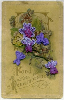Use a Victorian postcard printed on fabric as the background for this bouquet of French wired ribbon violets.