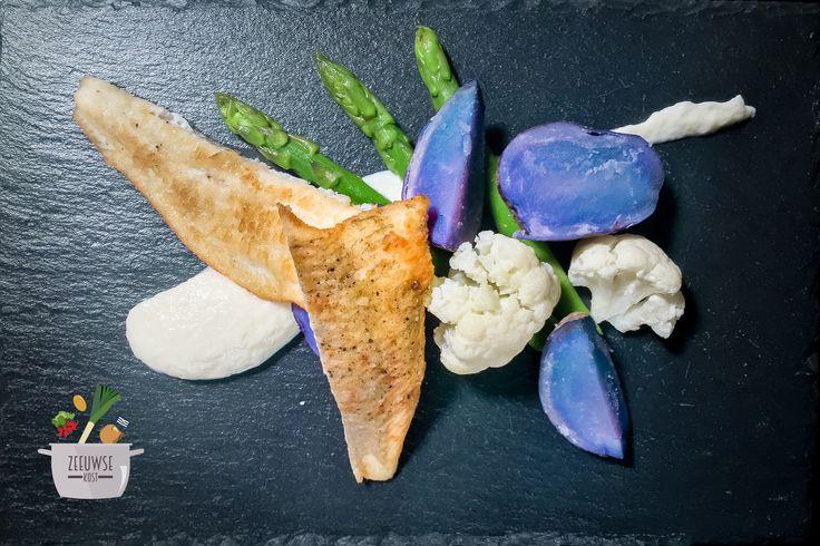 Een delicieus gerecht van truffelaardappel, gebakken schol, asperges met een crème van bloemkool.