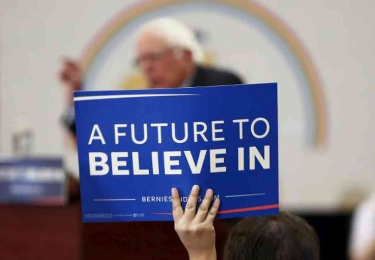 """Share or Comment on: """"USA: Sanders Wins Democrats Abroad"""" - http://www.politicoscope.com/wp-content/uploads/2016/03/Bernie-Sanders-Supporter-USA-Politics-Headline-News-Now.jpg - Sanders received 69 percent of the vote to earn nine of the 13 delegates at stake. Hillary Clinton won 31 percent, picking up four delegates.  on Politicoscope: Politics - http://www.politicoscope.com/2016/03/22/usa-sanders-wins-democrats-abroad/."""