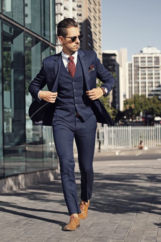Go for a navy three piece suit and a white oxford shirt for a classic and refined silhouette. Take a classic approach with the footwear and choose a pair of camel leather oxford shoes.   Shop this look on Lookastic: https://lookastic.com/men/looks/three-piece-suit-dress-shirt-oxford-shoes/19213   — Tan Leather Oxford Shoes  — Navy Three Piece Suit  — Brown Bracelet  — Brown Print Pocket Square  — Red Vertical Striped Tie  — White Dress Shirt  — Black Sunglasses