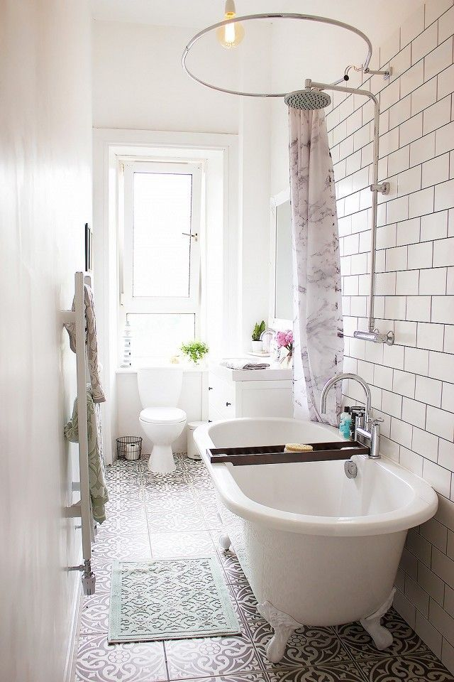 Small feminine bathroom with white subway tile, morrocean inspired floors, and a freestanding tub