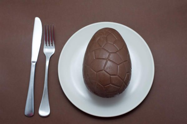 Love this image: Dessert serving of a whole chocolate Easter Egg on a white plate with knife and fork over a dark brown background - By stockarch.com user: easterstockphotos