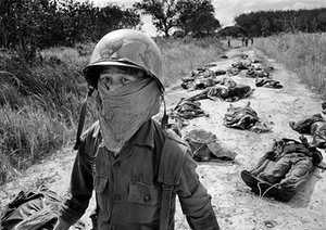A South Vietnamese stretcher-bearer wears a face mask to protect himself from the smell as he passes the bodies of U.S. and South Vietnamese soldiers killed fighting the Viet Cong in the Michelin rubber plantation, November 27, 1965. More than one hundred bodies were recovered after the Viet Cong overran South Vietnam's 7th Regiment, 5th Division, killing most of the regiment and several U.S. advisers. The plantation, situated midway between Saigon and the Cambodian border, was the scene of…