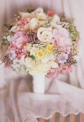 This bouquet is named Magnificent which it is. Flowers are filled with real gems, pearls and crystals.  Available in many colors. Vintage lace handle.