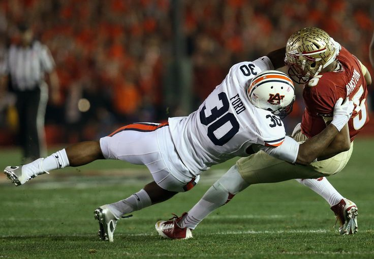 Quarterback Jameis Winston #5 of the Florida State Seminoles is sacked by defensive end Dee Ford #30 of the Auburn Tigers during the 2014 Vizio BCS National Championship Game at the Rose Bowl on January 6, 2014 in Pasadena, California.