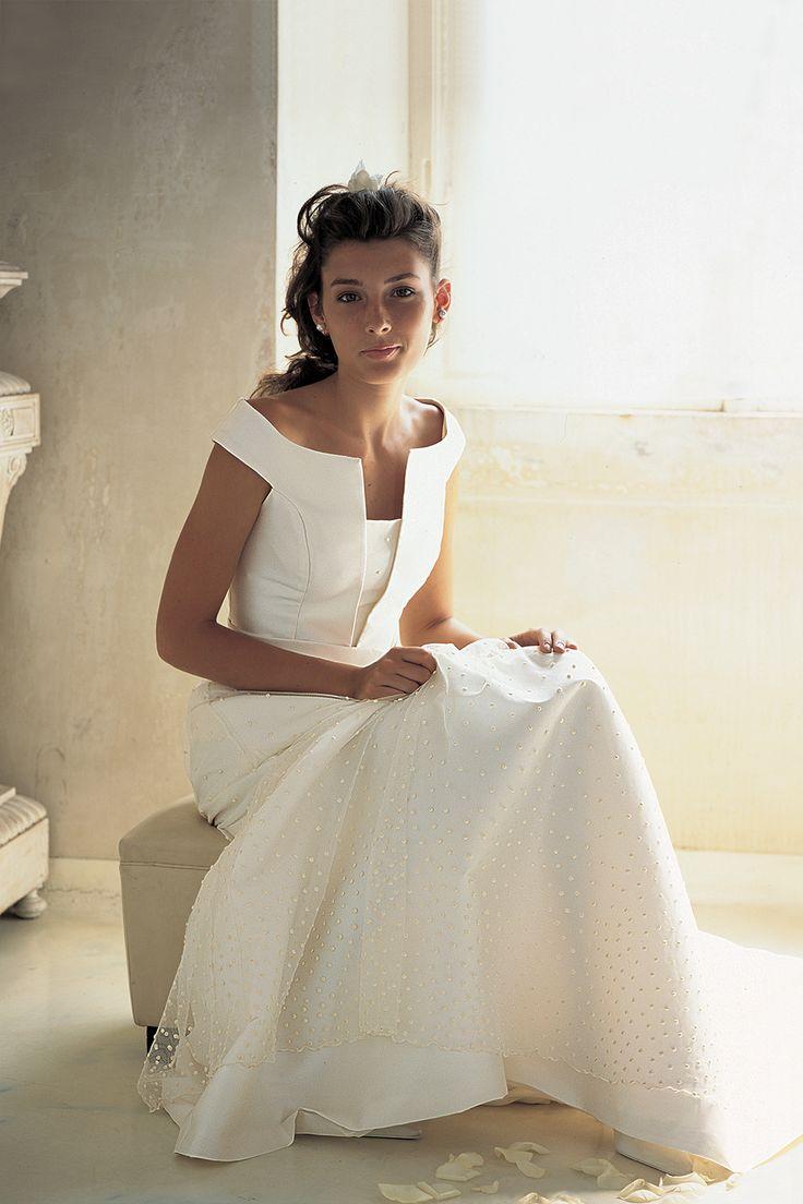 Realizzato interamente in Mikado e con una linea svasata, l'abito da sposa Giacinto è caratterizzato da un corpetto con una scollatura geometrica e da una cintura intrecciata in vita. Per la sposa che ama le forme geometriche, il look è da completare con un'acconciatura fermata da una Broche.