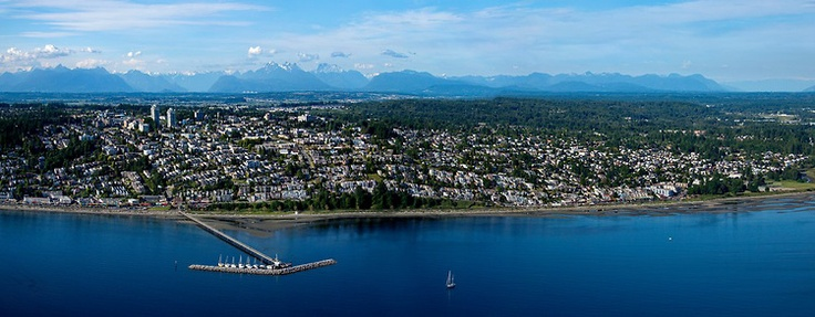 Gorgeous #WhiteRock Aerial Photo - OCEAN VIEWS an up close aerial panorama of White Rock with The Pier, and many of the houses up to 16th ave. Sailboat in the foreground and the coast mountains in the background.