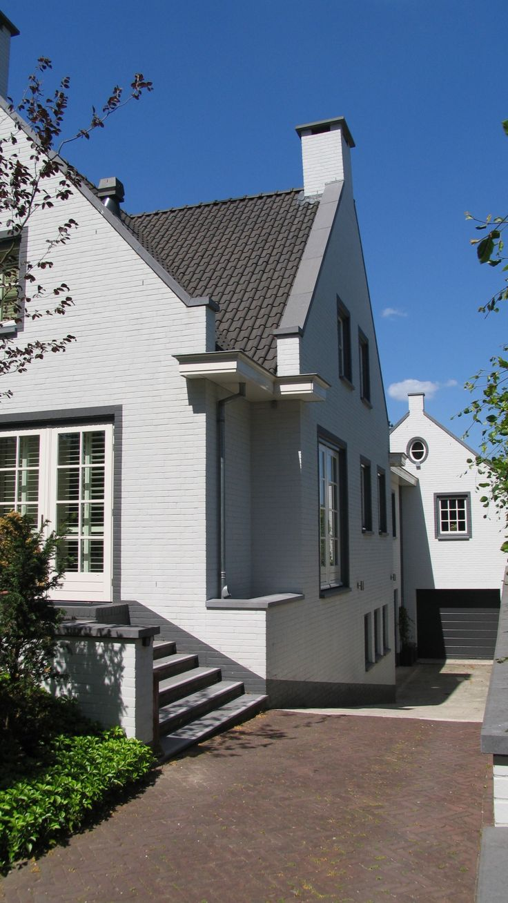 klassiek moderne woning   ruime wit gekeimde woning met grijze raamomlijsting, doorgestoken gevels en kenmerkende klassieke detaillering