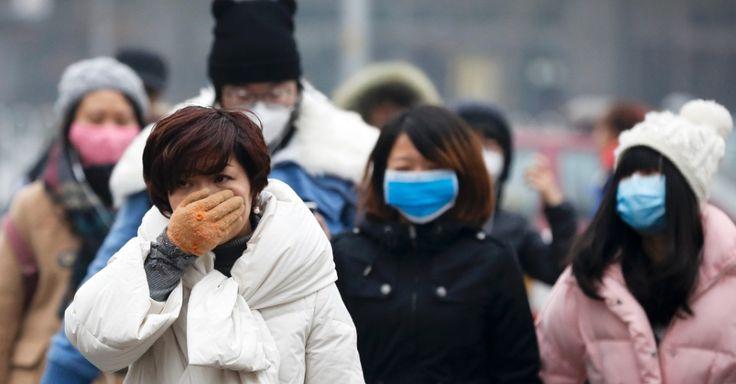 20151208 - Sem máscara, mulher usa a mão para cobrir parte do rosto e se proteger da poluição em Pequim. Entrou em vigor às 7h desta terça-feira, pela primeira vez, o alerta vermelho na capital chinesa, por causa dos altos índices de poluição no ar. Por conta disso, o trânsito e o barulho registrado hoje na cidade foram bem menores do que o normal. PICTURE: Andy Wong/AP
