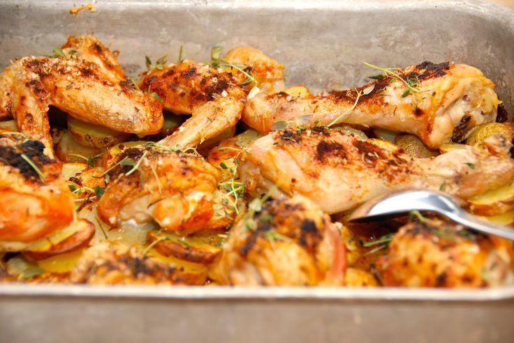 Kylling i fad er nem aftensmad, der laves i ovnen. Skær kartofler i skiver, og læg dem nederst i et ovnfast fad. Derpå lægger du så den parterede kylling, og steger det hele i ovnen. Foto: Guffeliguf.dk.