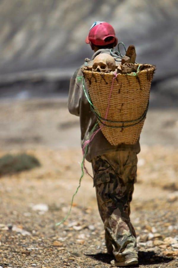 Un homme de l'ancien royaume de Mustang dans le nord de Népal, porte des restes humains découvertes dans une crypte funéraires