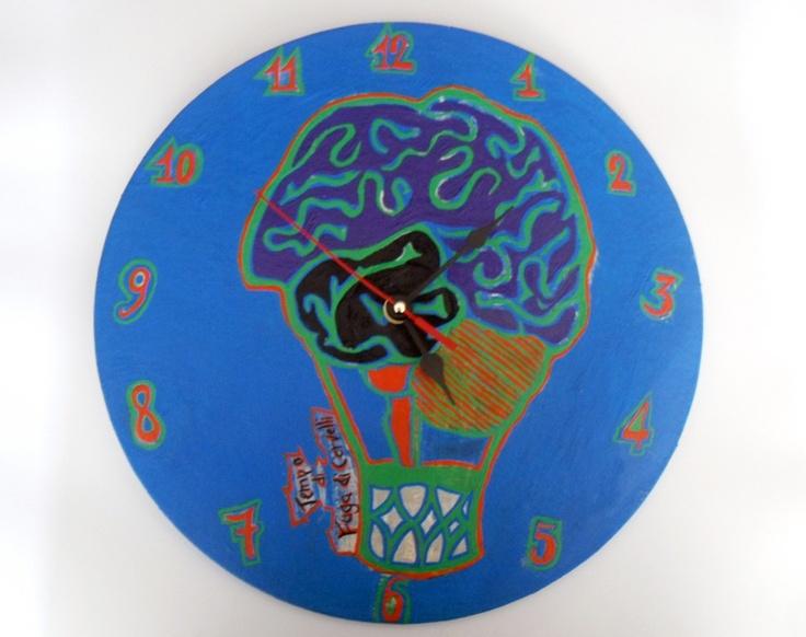 Orologio da parete, dipinto a mano, su vari cartoni di recupero. Molto resistente, presenta un tema decorativo vagamente satirico che conferisce originalità, ironia  e contemporaneità al semplice complemento d'arredo. Raffigura un cervello che ha preso la forma di una mongolfiera ma anche la funzione perché sta volando. La creatività ci ha spinto realizzare questo soggetto sarcastico e a portarlo all'interno dell'eco design.
