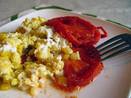 Scrambled eggs with corn, goat cheese, and roasted tomatoes.