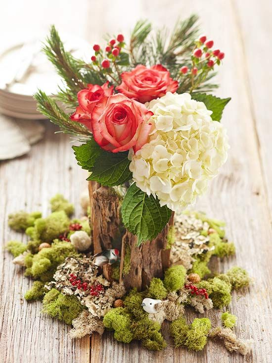 "Put a twist on typical holiday table decor with a tree-inspired centerpiece. To create the trunk, wrap a clear glass vase with bark chips. At the base of the trunk, add faux variegated moss and top with nuts, berries, and tiny decorative birds to mimic a forest setting. Bring the ""tree"" into bloom with a lush floral arrangement of hydrangeas, roses, fresh greenery, and hypericum berries./"