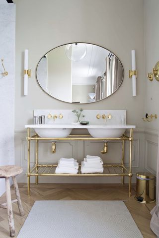 Architectural Digest - bathrooms - gray bathroom, gold and gray bathroom, oval mirror, large oval mirror, long sconce, long brass sconce, br...: Gold Fixtures, Hemmings Hotels, Gold Accent, White Bathroom, Brass Bathroom, Herringbone Floors, A Hemmings, Gray Bathroom, Double Sinks
