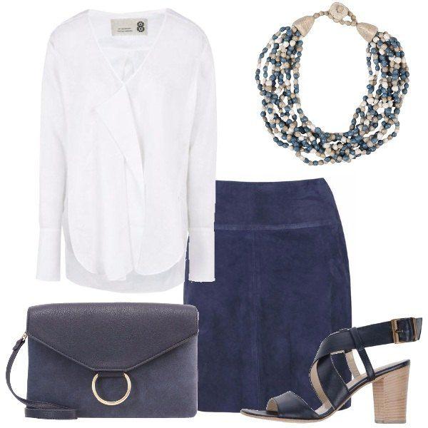 Una blusa bianca in lino, a maniche lunghe e collo a V, è abbinata ad una gonna di camoscio blu, lunghezza al ginocchio, sandali blu con tacco di legno geometrico, tracolla in ecopelle blu, collana in carta e legno, grigia con perline colorate.