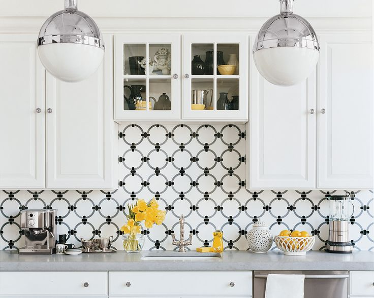 An all-white kitchen gets an instant upgrade with an intricate mosaic backsplash in a cool black and grey palette. Pendants complete this look.