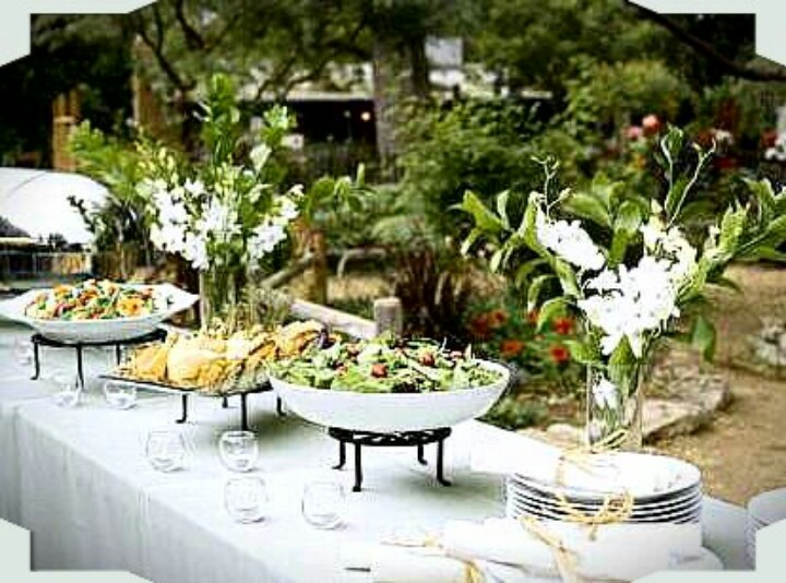 Outdoor Buffet Table. Who would of guessed to use scrolled iron PLANT STANDS as food bowl risers! Cute.