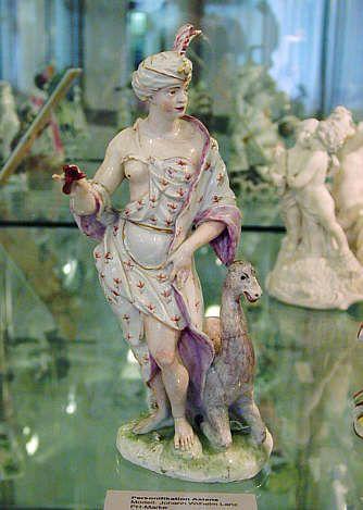"""Allegorien """"Die vier Erdteile""""  Asien  Leicht bekleidete Frauengestalt mit indisch anmutendem Turban und Blüte in der Hand, das kniende Tier zu ihren Füßen soll wohl ein Kamel darstellen  J. W. Lanz, Modell 1750-55, Ausformung 1755-59  Erkenbert-Museum, Frankenthal"""