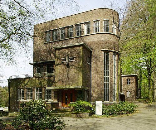 Dit gebouw ontworpen in de stijl van de 'Haagse School' is een juweel. Het staat in het deelgebied De Brink van Arnhems Buiten, ook wel bekend als Arnhems Businesspark. De specifieke bouwstijl die bloeide van 1925 tot 1940 kenmerkt zich door een strakke vormgeving in combinatie met een luxueuze uitvoering. Bakstenen gebouwen met krachtige horizontale lijnen van kozijnen en gevelbanden onderbroken door de verticale lijnen van bijvoorbeeld een trappenhuis.