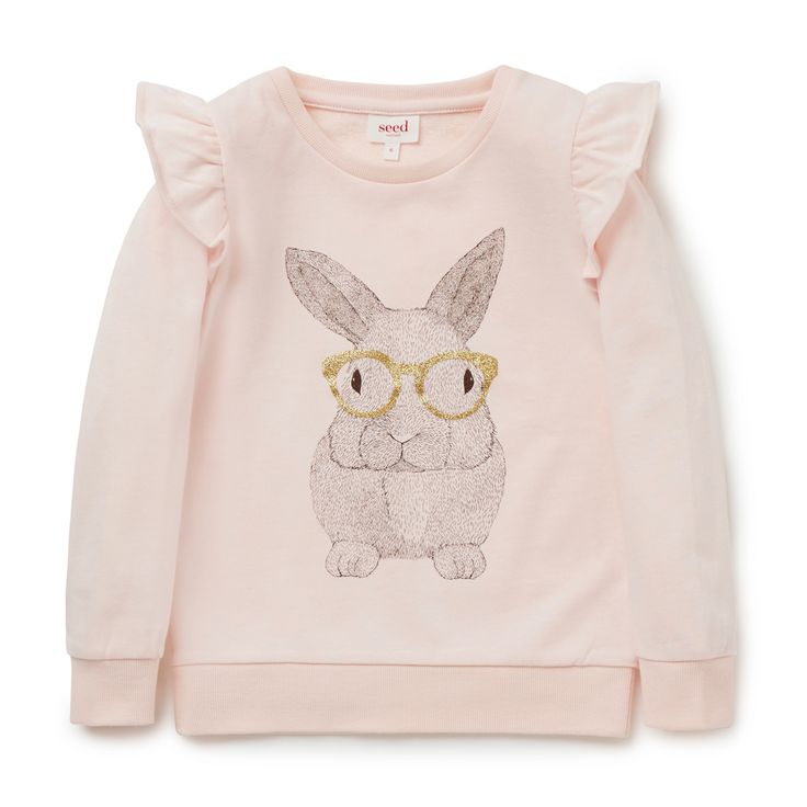 100% Cotton French Terry. Long sleeve windcheater features front placement bunny print motif with frill shoulders. Regular fitting silhouette. Available in Soda Pink.