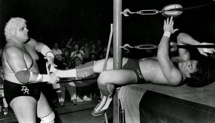 Dusty Rhodes (left) was one tough son of a plumber when it came to wrestling. Here, Dusty Rhodes tries to drag Tully Blanchard out for a little action beyond the ring during a match at the Charlotte Coliseum.' 1985.