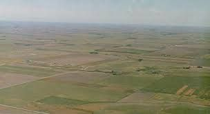 Plains occur as lowlands and at the bottoms of valleys but also on plateaus or uplands at high elevations. In a valley, a plain is enclosed on two sides but in other cases a plain may be delineated by a complete or partial ring of hills, by mountains or cliffs.