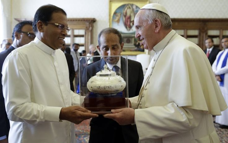 Pope Francis is presented with a gift by President Maithripala Sirisena during a private audience at the Vatican in December last year (AP Photo/Gregorio Borgia, Pool)