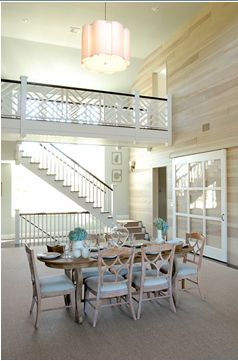 Love this two-story dining room in the Hamptons. The hint of turquoise is perfect in this room because of the natural light. This dining room seamlessly brings the outdoors in with the sky-high ceilings, light wood finishes, and soft hues.