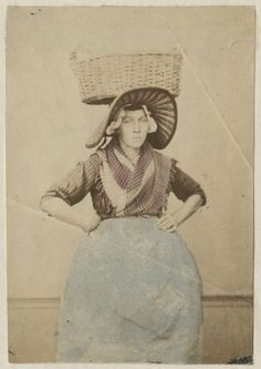 Vrouw in Scheveningse klederdracht; negotiante (visverkoopster) met vishoed en vismand, zij draagt een muts met lange afhangende klappen en een ijzer met stukken, zij draagt het haar in een toer. ca 1890