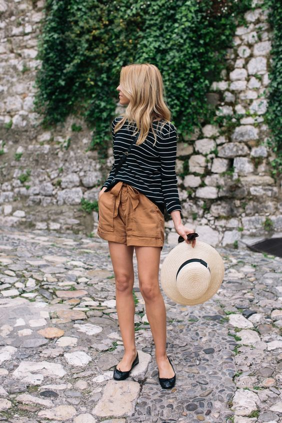 This combo of a black and white striped long sleeve t-shirt and brown shorts will attract attention for all the right reasons. Black leather ballerina flats will add some edge to an otherwise classic look.   Shop this look on Lookastic: https://lookastic.com/women/looks/long-sleeve-t-shirt-shorts-ballerina-shoes/20972   — Black and White Horizontal Striped Long Sleeve T-shirt  — Black Leather Crossbody Bag  — Brown Shorts  — Beige Straw Hat  — Black Leather Ballerina Shoes