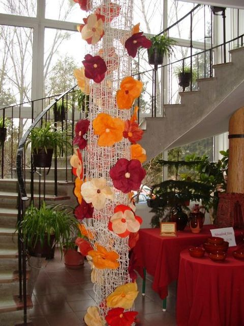 Virág-oszlop    Látványos+dekoráció+készülhet+kisebb-nagyobb,+különböző+színű+papírvirágok+felhasználásával. Összetekert+háló+alapra+vannak+rögzítve+a+virágok,+melyek+gyűrt+papírból+készültek.+Mint+a+fotón+is+látható,+a+sárgás-vöröses-barnás…