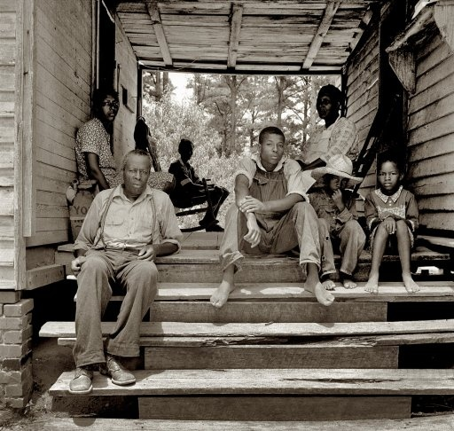 """July 1939. """"Zollie Lyons, Sharecropper, home from the field for dinner at noontime, with his wife and part of his family. Wake County, North Carolina."""" by Dorothea Lange"""