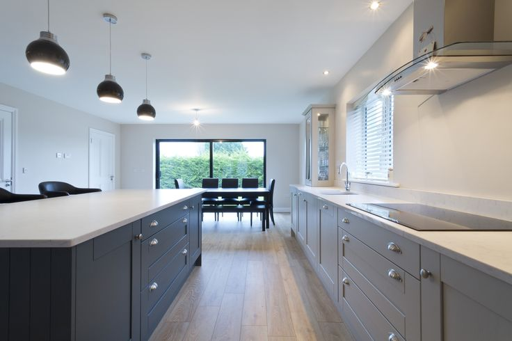A classic style with a minimalist twist, this kitchen makes perfect use of the large open space. The two prominent colours, Purbeck Stone and Downpipe by Farrow & Ball, compliment one another while distinguishing separate work spaces while the Lagoon Silestone worktop then ties the two together.